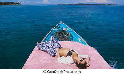 Close up of attractive model sunbathing on the deck of small yacht in the open sea. Young girl dressed in black swimsuit, blue trousers and black sunglasses is lying on rostrum of a ship and enjoying her cruise.