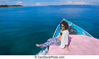 The girl on the island of Bali tours. She sits on the edge...