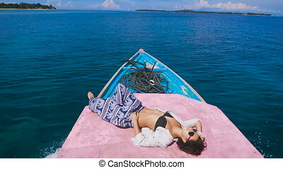 Cute girl lying in the front of a motor boat enjoys walking...