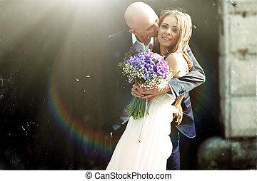 Bride looks fabulous being kisses by a groom in the sunshine