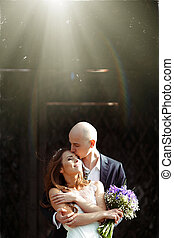 Groom kisses bride's forehead while sun shines over them
