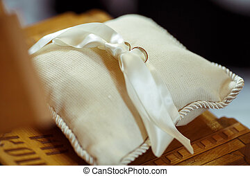 Wedding rings lie on a simple white pillow