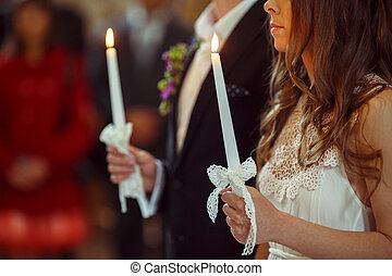 A wedding couple pray during an engagemnt ceremony holding candles in their hands