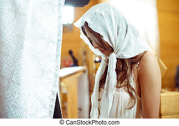 Bride in a white shawl prays before a priest standing on the knees