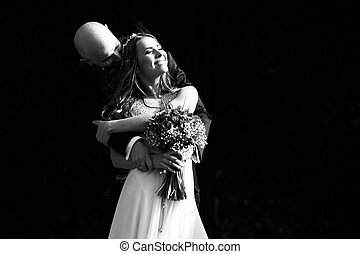A black and white picture of a wedding couple hugging and...