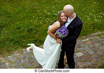Groom kisses bride's forehead while she leans to him smiling