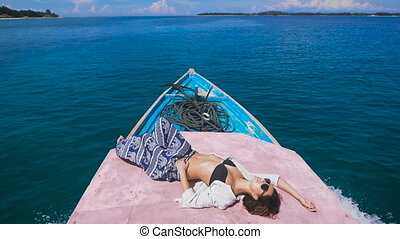 Tanned young girl in sunglasses with a thrown back arm behind her head is in the stern of the boat, which quickly goes on the dark blue ocean to a small island