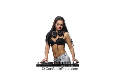 DJ Girl brunette plays the DJ console and dancing. White...