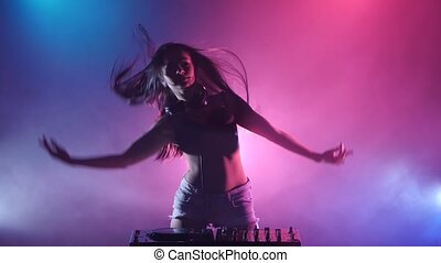 girl DJ starts dancing blue pink lights and a lot of smoke -...