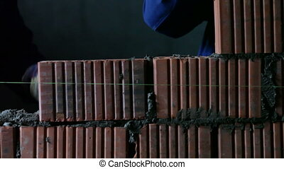 builders lays bricks on a construction site
