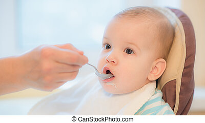 grandmother gives baby food from a spoon