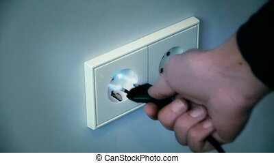 Electricity shock from a wall socket - A male hand reaching...