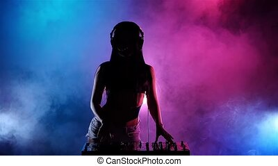 Girl sexy DJ with headphones playing on turntables. Slow motion