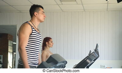 Fitness man and woman walking on treadmill in gym