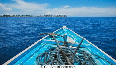 Blue boat with an anchor and a long rope on board, swaying...