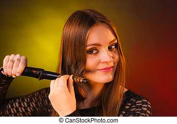 Happy woman curling her long brown hair - Haircare,...
