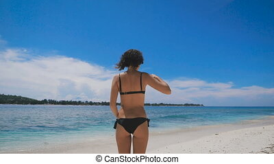 Tanned girl with slim figure standing with his back to the camera and looking into the distance. Curly brunette straightens your hair on the sandy beach near the blue ocean.