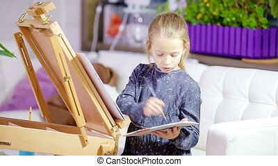 Adorable little girl painting a picture on easel indoor