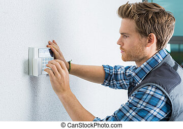 handsome young electrician repairing intercom