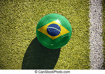 football ball with the national flag of brazil lies on the field