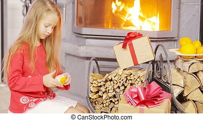 Happy nice girl opening christmas present near fireplace