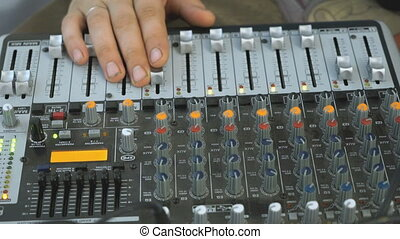 DJ working on a audiomixer at a nightclub. Hands adjusting...