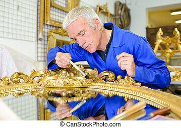 Man restoring gilt mirror