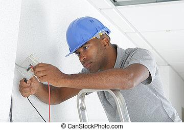 man installing wiring