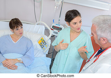 Patient in hospital bed, medical staff in discussion