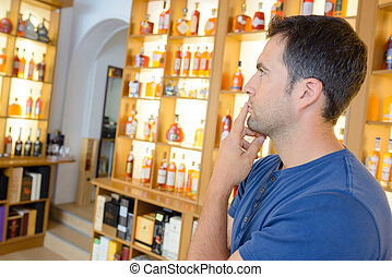 Man contemplating bottles in liquor store