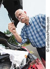 elder man servicing his car at home