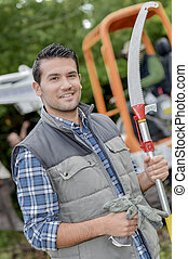 Gardener holding gloves and pruning saw