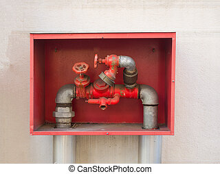 building's fire hose connections with red handles in a red...