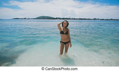 Cheerful girl fooling around while standing in water. Funny dance of cute brunette at a shallow depth in the ocean. Young woman enjoys her leisure at the resort.