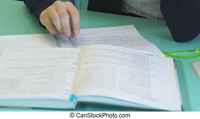 The schoolgirl decides the home task in a notebook during...