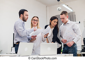 Group of four diverse men and women in casual clothing talking in office