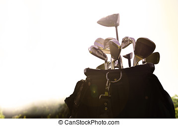 Golf bag with irons with the sun shining on it at a golf...
