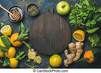 Oranges, mint, lemons, ginger, honey, apple, wooden board in...