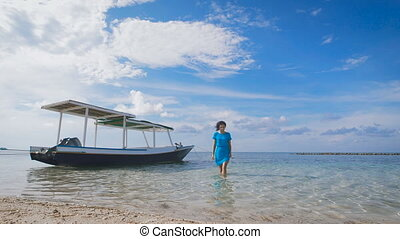 Beautiful girl in blue dress walking on the water near the moored boats. Slim brunette walks close to the sandy beach. Young woman relaxing on a tropical resort.