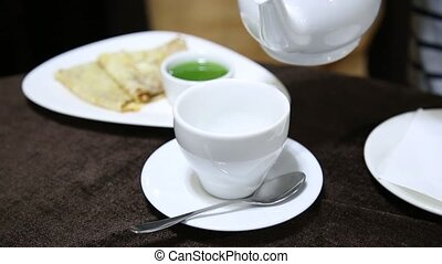 Pouring tea into white cup on table from porcelain kettle....