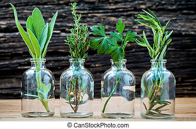 Bottle of essential oil with herbs rosemary, sage,parsley  and thyme  set up on old wooden background .