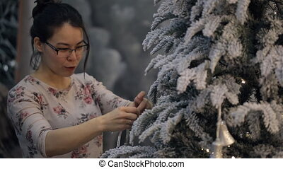 Asian woman decorates Christmas tree, speaks, smiles...