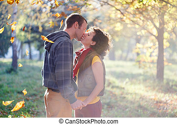 Loving couple kissing in the park in the sunlight on trees...