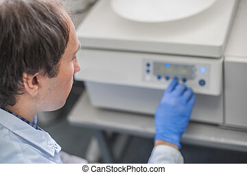 Technician uses the centrifuge machine in the medical or...