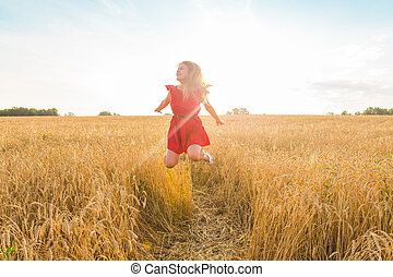 Woman jumps to the sky in yellow field at sunset
