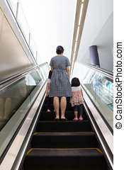 Asian Chinese mother and daughters taking escalator at MRT...