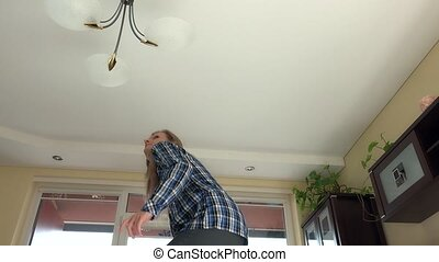 housekeeper woman climb up and change light bulbs in chandelier.