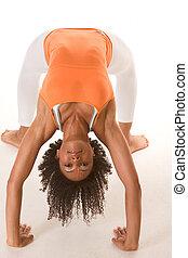 Ethnic female in sport clothes performing bridge exercise