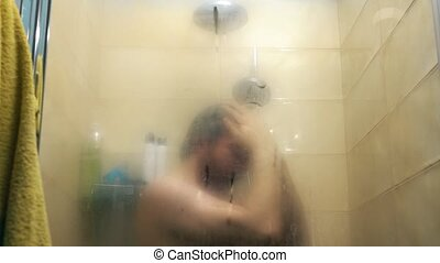 Man taking shower behind misted glass. Slow motion video,...