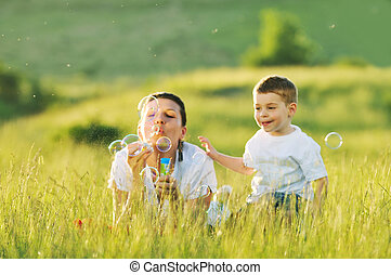 woman child bubble - happy child and woman outdoor playing...